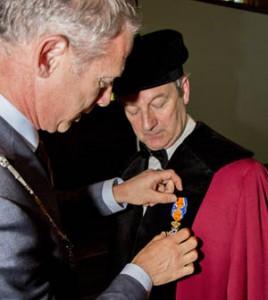 Burgemeester Onno Hoes speldt een lintje op bij Ton Gorgels