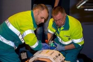 Twee ambulancemensen zitten bij een reanimatiepop en geven beademingen met een ballon en masker. De AutoPulse is aangesloten voor borstcompressies.