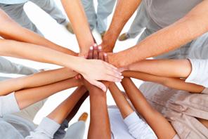 bovenaanzicht van het midden van een cirkel mensen, die hun handen op elkaar leggen als symbool van samenwerking