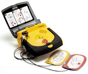 Een AED met de klep open en de elektrodeplakkers ernaast