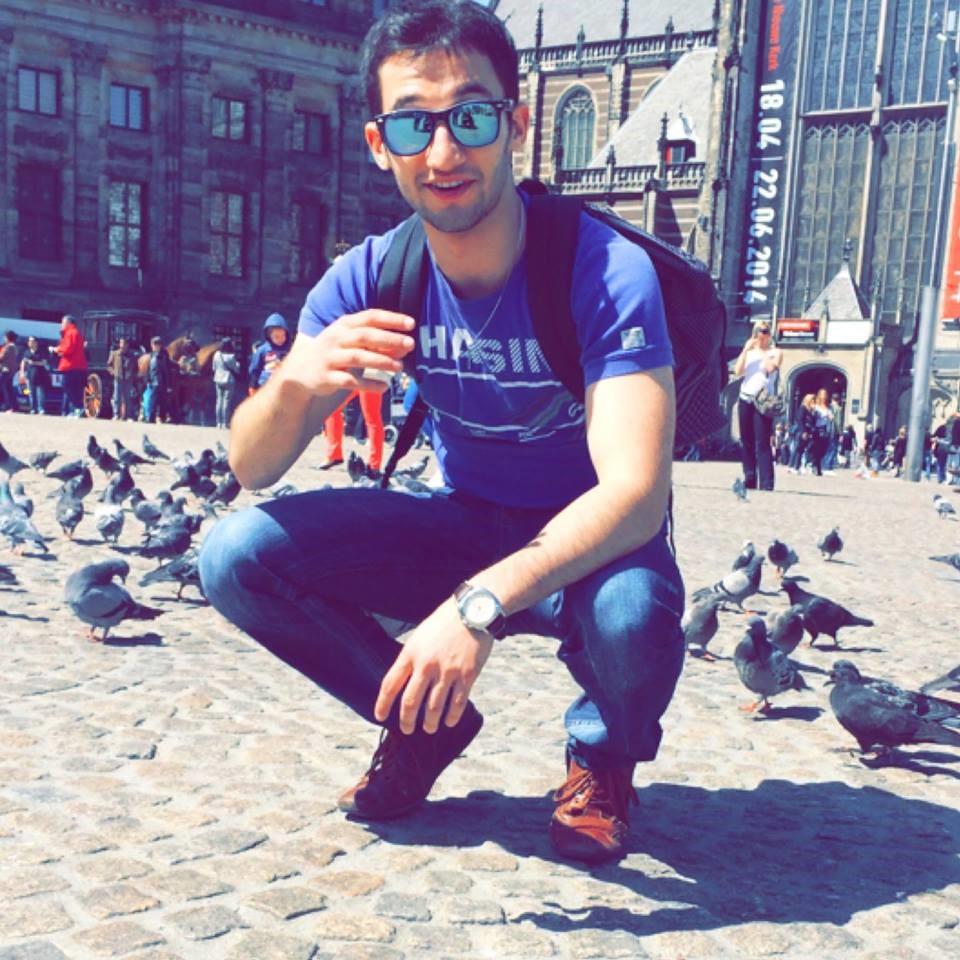 Bashar Razoki hurkend op een plein met duiven