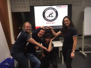 instructeurs van taskforce qrs nijmegen staan lachend voor een presentatiescherm met hun logo en ze vormen met hun armen de vorm van een hart