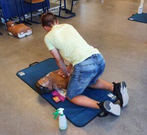 Een scholier oefent borstcompressies op een reanimatiepop. Een mobiele telefoon ligt bij het hoofd.