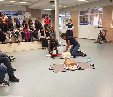 Instructeur van Taskforce QRS Amsterdam demonstreert borstcompressies op een reanimatiepop voor een tiental middelbare scholieren.